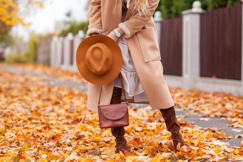 Frauenmode im Herbst mit Hut, Mantel und Handtasche