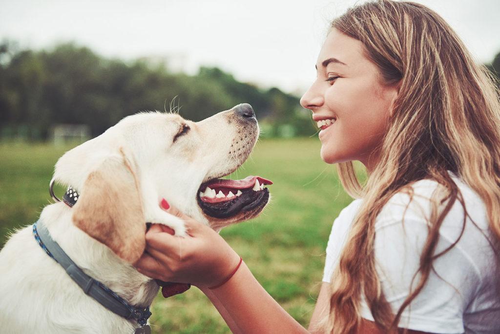 Frau und Hund, die sich angrinsen