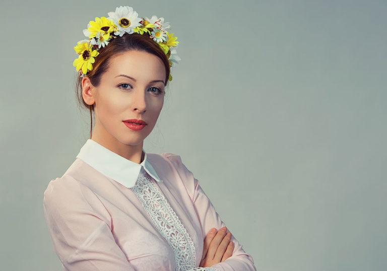Frau mit Hemd und einem gelb-weißen Blumenkranz