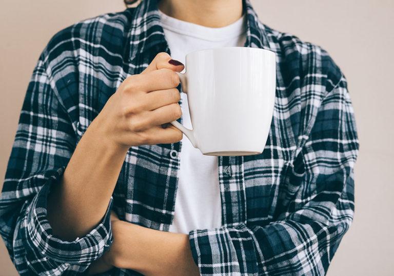 Frau in einem Flanellhemd hält eine Tasse